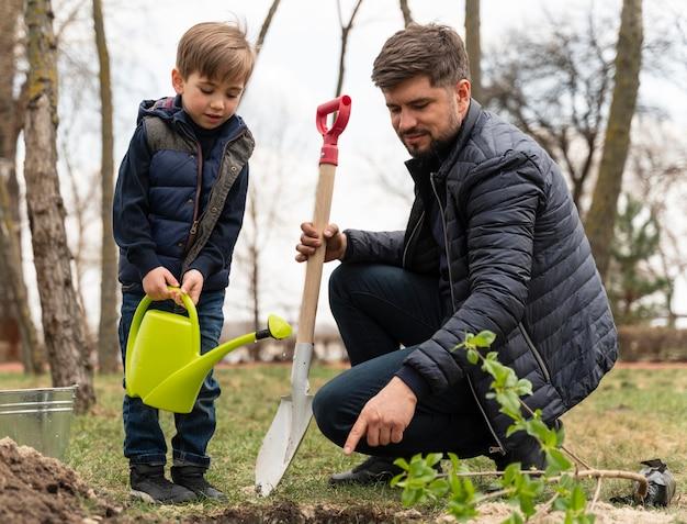 Человек втыкает в землю небольшое дерево
