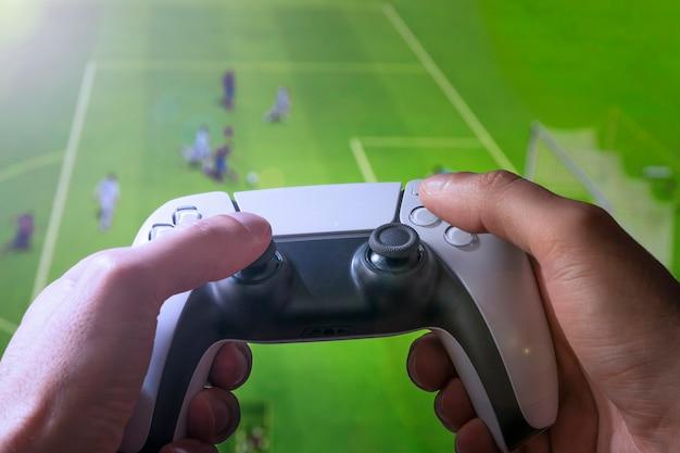 男はビデオゲームコントローラーでサッカーゲームをします。