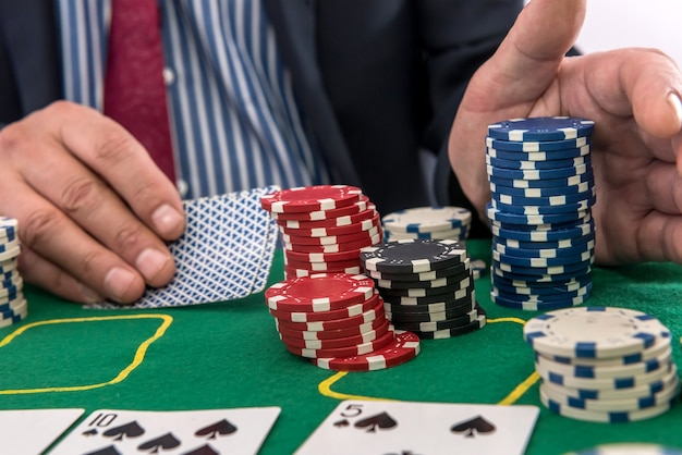 Man play in casino with playing cards and chips at green table. gambling