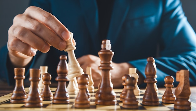 Man play chess on the board on the grey background