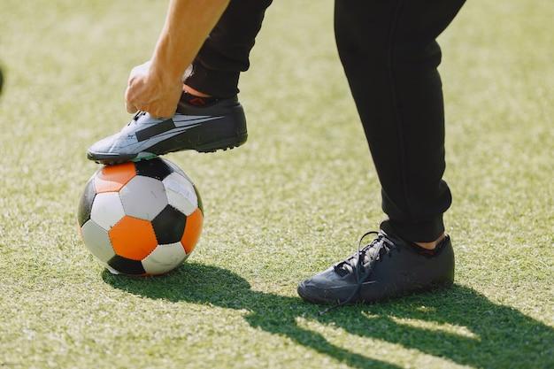 Человек играет socerl в парке. турнир по мини-футболу. парень в черном спортивном костюме.