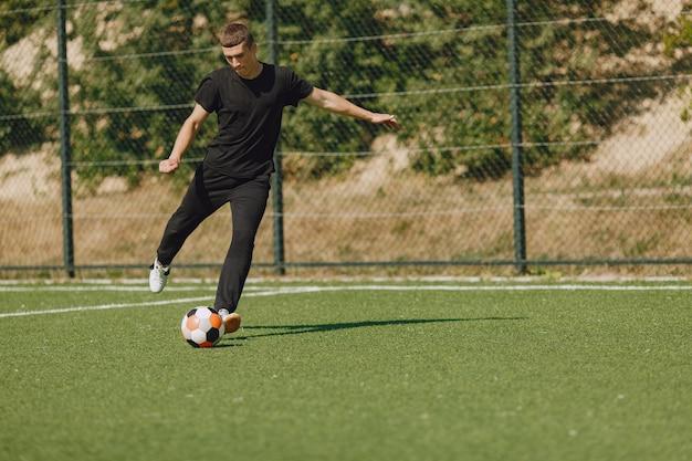 男は公園でソセルをします。ミニサッカーのトーナメント。黒のスポーツスーツを着た男。