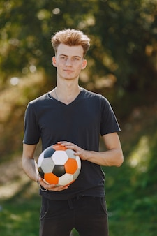 L'uomo gioca a socerl al parco. torneo su mini-footbal. ragazzo in tuta sportiva nera.