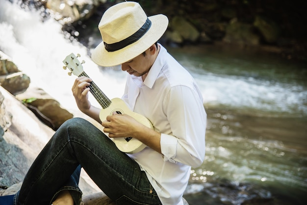 Man play ukulele new to the waterfall