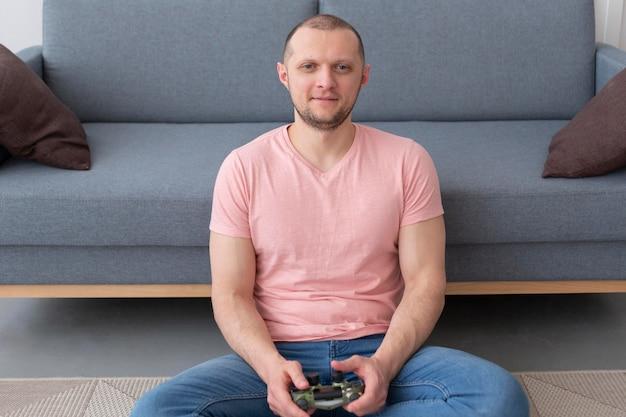 家でビデオゲームをしている男