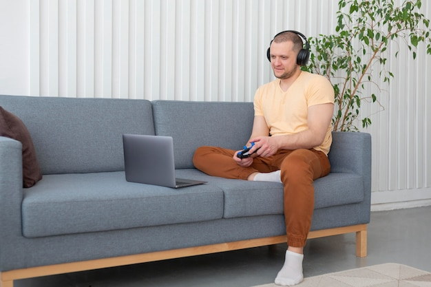 彼のラップトップでビデオゲームをプレイしている男