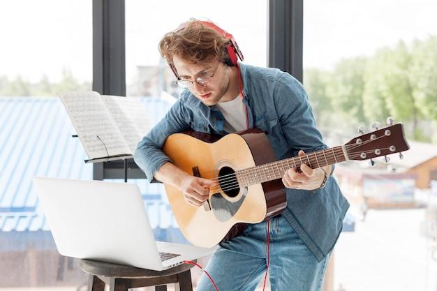 家でアコースティックギターを弾く男