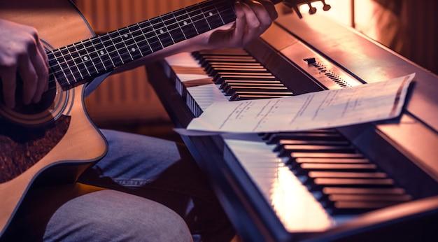 Человек играет на акустической гитаре и фортепиано крупным планом, записывает ноты, красивый цветной фон, концепция музыкальной деятельности