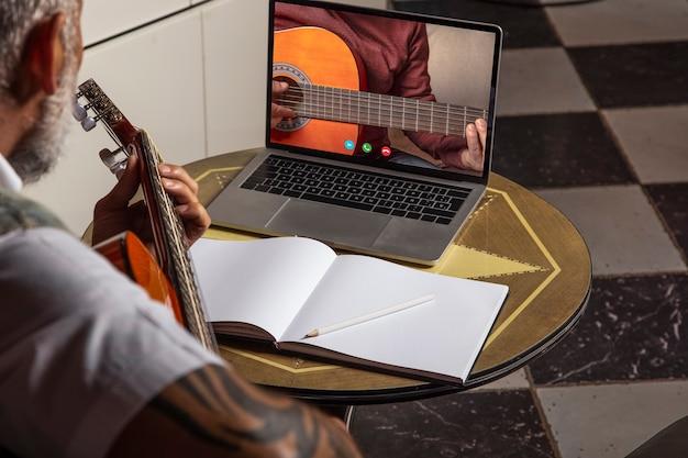 집에서 연습하는 동안 어쿠스틱 기타를 연주하고 노트북으로 온라인 수업을 보는 남자..온라인 교육, 온라인 수업.