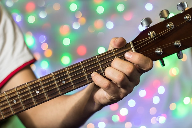Man playing on acoustic guitar, closeup fingers on guitar neck against christmas blurred bokeh lights on background