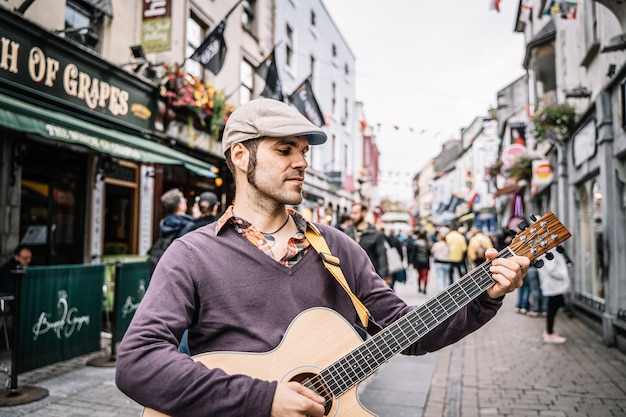 Man playing the acoustic guitar on a pedestrian street.