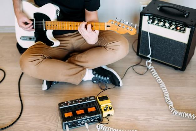Человек играет на электрогитаре в студии
