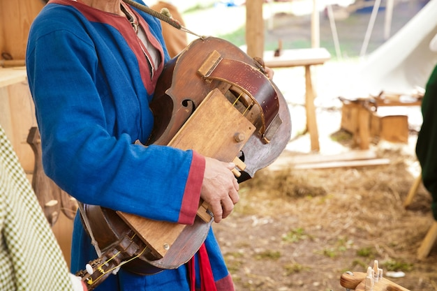 Man playing the ancient stringed instrument, reconstruction of ancient times