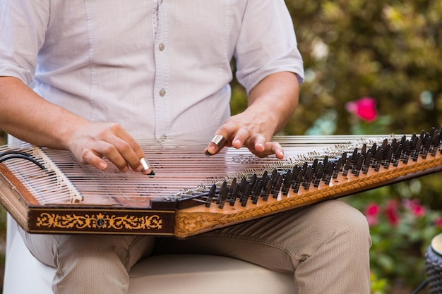 A man playing an arabic musical instrument
