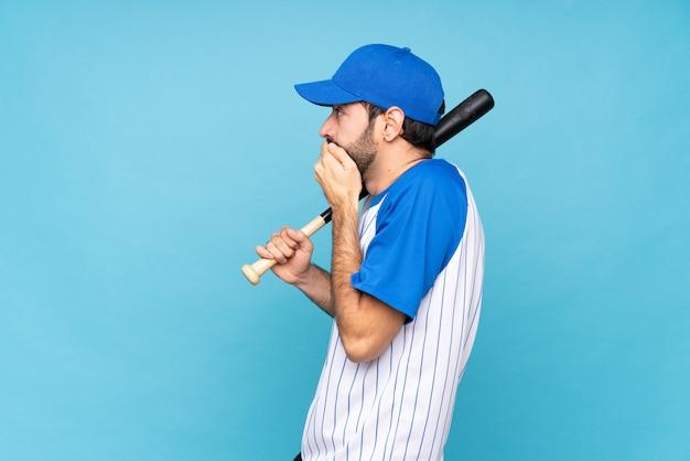 Man playing baseball over isolated wall