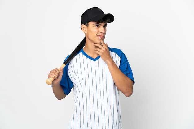 Man playing baseball over isolated white background having doubts while looking up