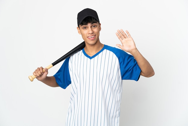 Man playing baseball over isolated white background saluting with hand with happy expression