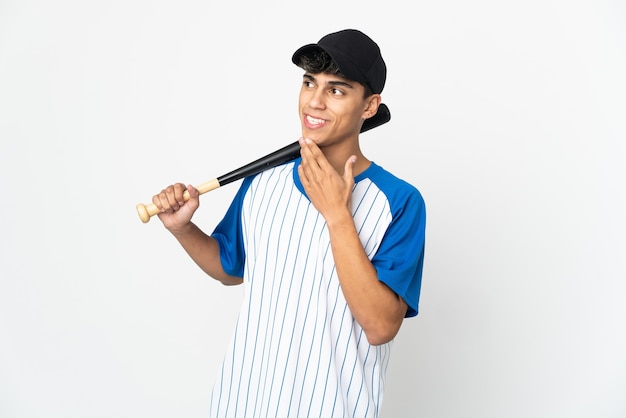 Man playing baseball over isolated white wall looking up while smiling