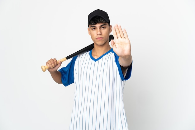 Man playing baseball over isolated white wall making stop gesture