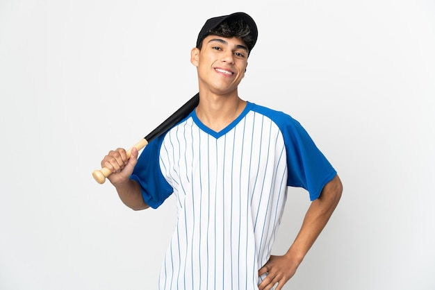 Man playing baseball over isolated white wall posing with arms at hip and smiling