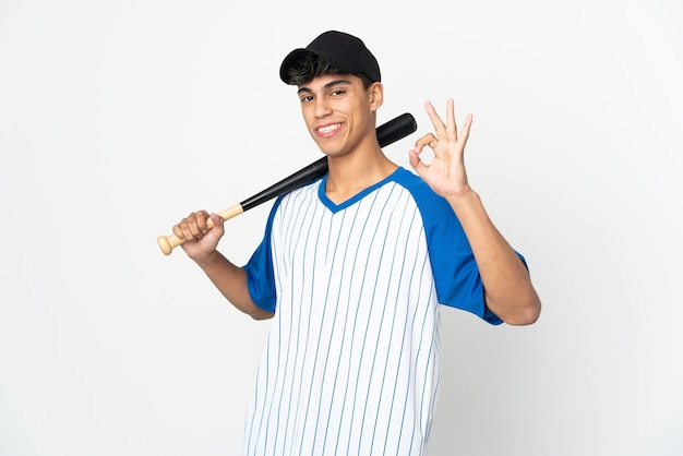 Man playing baseball over isolated white wall showing ok sign with fingers