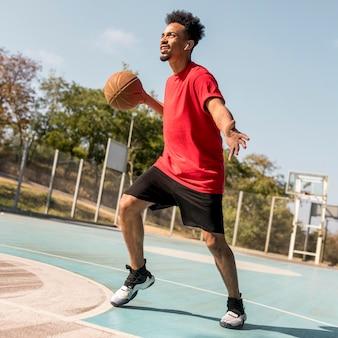 Человек играет в баскетбол на поле