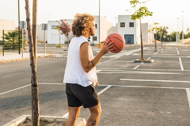 通りにバスケットボールをしている男