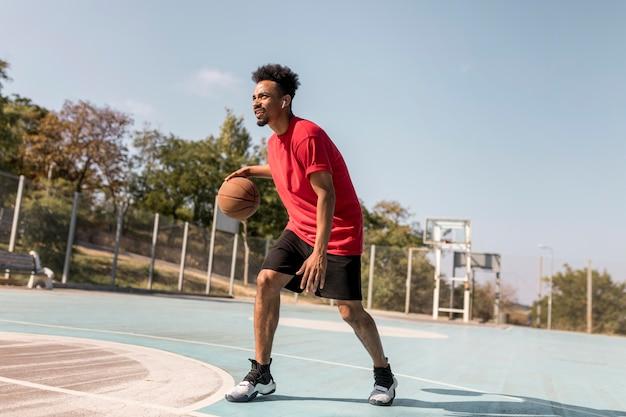 Человек играет в баскетбол на открытом воздухе
