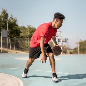 Человек играет в баскетбол на улице