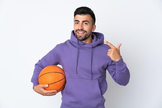 Человек играет в баскетбол над изолированной белой стеной, показывая большой палец вверх