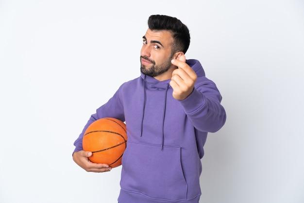 Человек играет в баскетбол над изолированной белой стеной, делая денежный жест