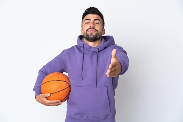 かなり閉じるために握手する孤立した白い壁の上でバスケットボールをしている男