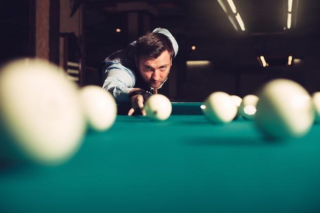Человек играет в бильярд