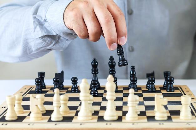 チェスゲームをしている人、チェス盤でチェスの駒を手で動かします。成功する金融ビジネス戦略の概念