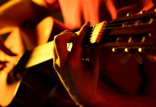 Uomo che suona la chitarra classica su una vista ravvicinata di un concerto musicale di scena