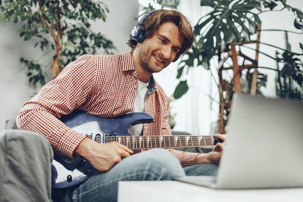 自宅でエレキギターを弾き、ラップトップに音楽を録音する男性