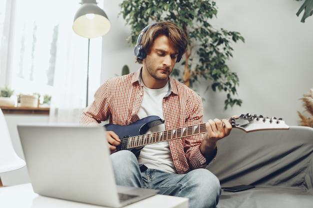 電気ギターを弾くとラップトップに音楽を録音する男