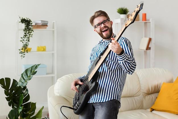 自宅でエレクトリックギターを弾く男