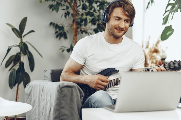 Man playing electric guitar and recording music into laptop at home