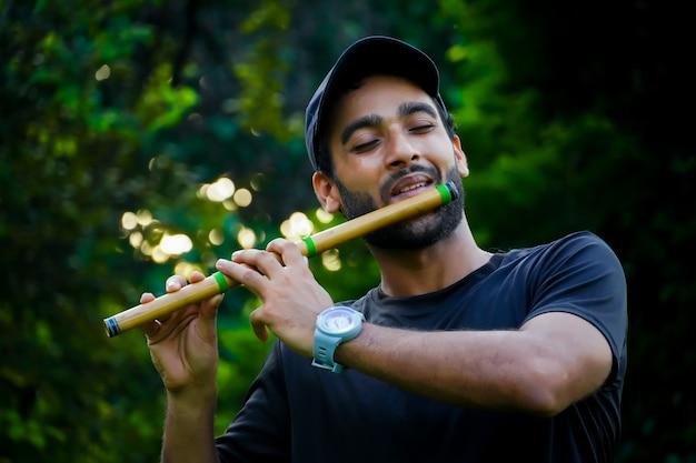 Человек играет на флейте в красивом фоне
