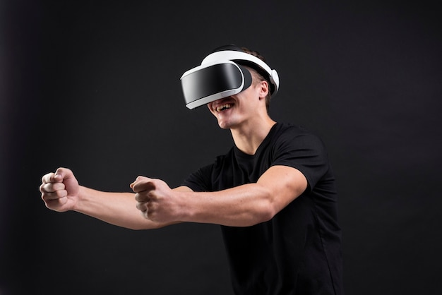 Man playing games with vr goggles black background