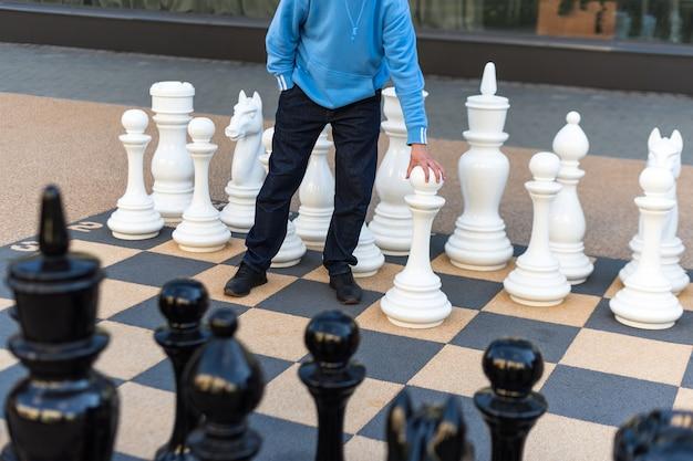 屋外で巨大なチェスをしている男