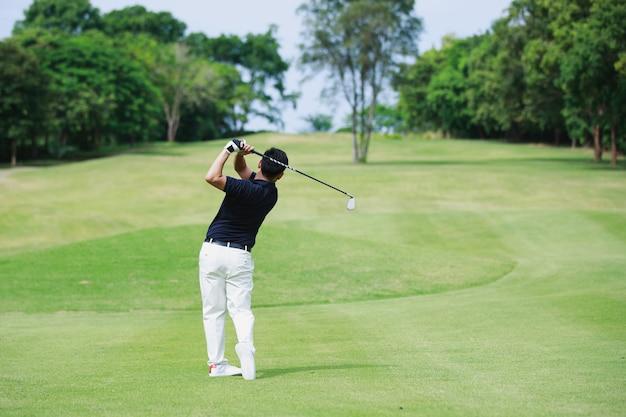 Человек играет в гольф на поле для гольфа