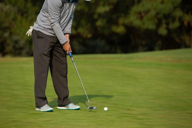 Человек играет в гольф, паттинг-грин