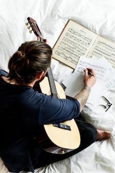 Man playing a guirtar composing