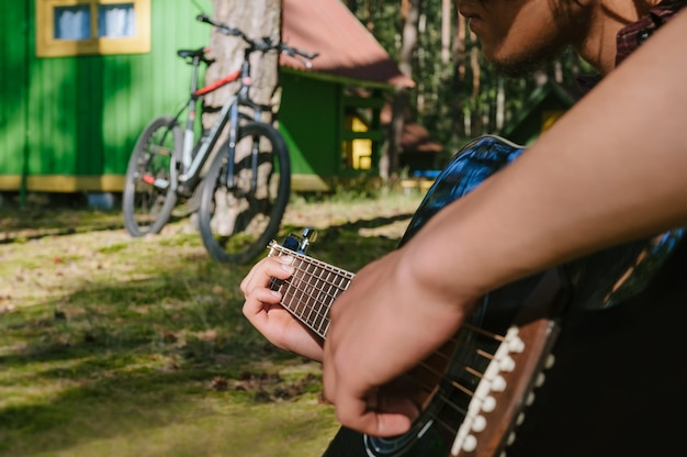 Man playing the guitar. against the background of a forest house in nature.