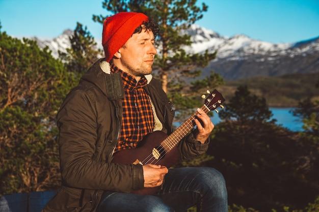 산 숲과 호수를 배경으로 기타를 치는 남자는 셔츠를 입는다