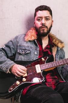 ギターを弾くとカメラマンを見て男