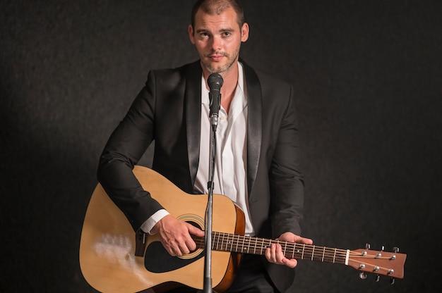 男はギターを弾き、マイクで歌う