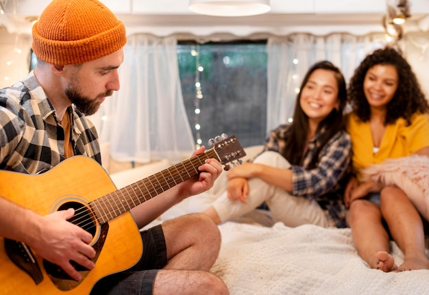 Мужчина играет на гитаре и женщины слушают